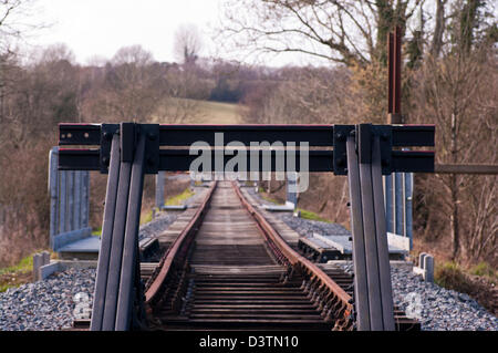Empty Straight Single Track End Of The Railway Line With Buffers (Shallow depth of field focus on the bumpers) - Stock Photo