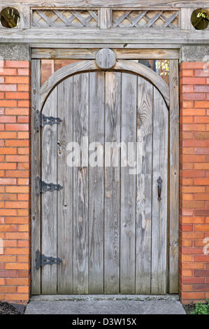 Wooden door with rounded top in brick wall close up, a garden gate shut and locked. - Stock Photo