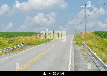 Country road heading over a hill under sunny blue skies with white clouds, a two lane summer highway in rural Pennsylvania, PA,