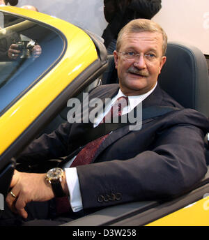 Porsche CEO Wendelin Wiedeking (R) sits with a smile in a yellow Porsche 911 Carrera 4S convertible prior to the - Stock Photo