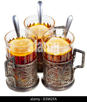 retro glasses in old cupronickel glass holders with black tea and lemon isolated on white background