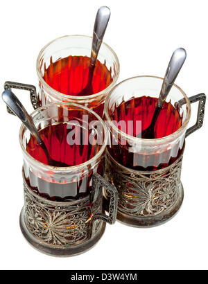 three retro glasses in silver glass holders with spoon with black tea isolated on white background
