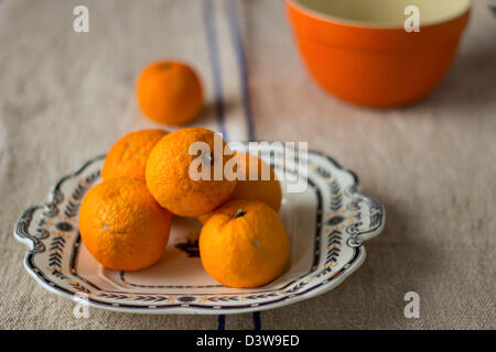 Oranges sitting on a Wedgewood decorative plate on a blue-striped linen tablecloth with an orange bowl in the backgroound. - Stock Photo