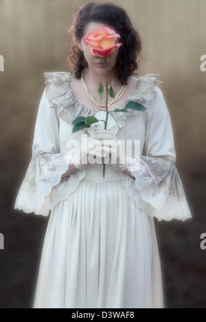 a lady in a victorian dress is holding a rose in front of her face - Stock Photo