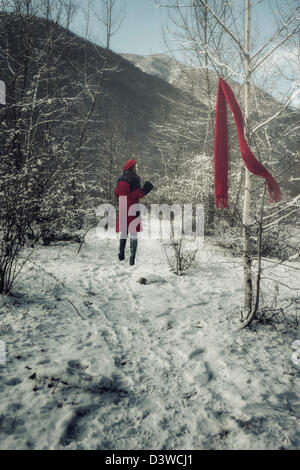 a young woman in a red coat is running through a wintery forest and lost her red shawl - Stock Photo