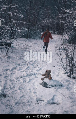 a teddy bear is sitting in the snow, a girl is running away - Stock Photo