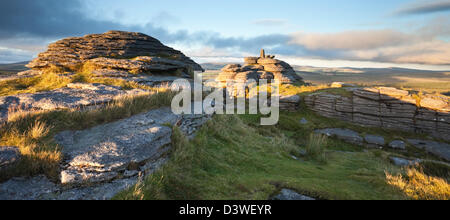 The last of the warm light from the setting sun paints its glow over Bellever tor - Stock Photo