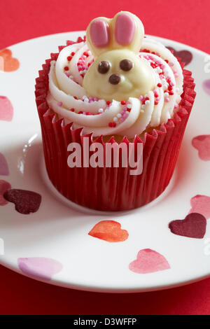Easter cupcake with white chocolate bunny rabbit on set on plate with hearts on - Stock Photo