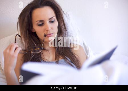 Brunette woman engrossed in reading a book while in her room - Stock Photo