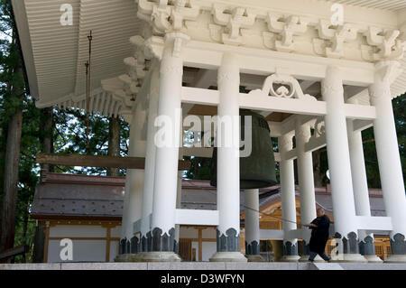 Buddhist monk ringing giant bell in Dai Garan at Kongobuji (Temple of Diamond Mountain), head temple of Koyasan - Stock Photo