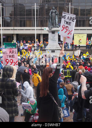 A woman holds a placard in the air proclaiming 'We are the 99%' during a protest in guildhall square, Portsmouth, England.