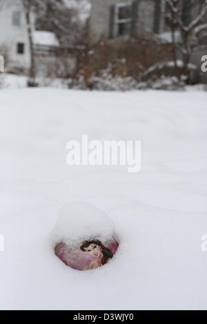 A child's ball buried halfway in the snow.