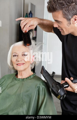 Hairdresser Blow Drying Woman's Hair - Stock Photo