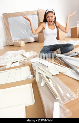 Multiracial Asian Caucasian frustrated young woman moving in new home trying to assemble table - Stock Photo