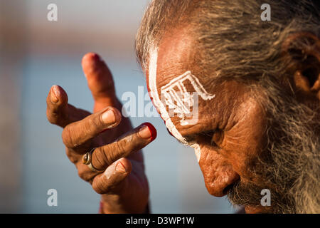 Sadhu painting his face with the word for God on his forehead at the Kumbh Mela, Allahabad, India - Stock Photo