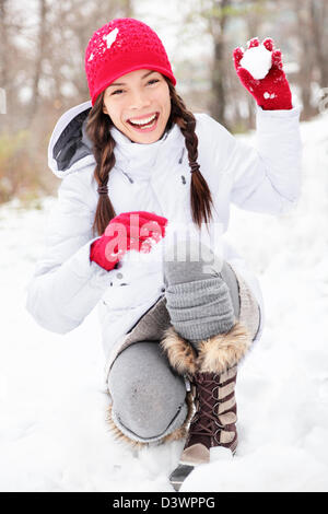 Beautiful joyful Asian Caucasian woman playing in snow throwing snowball at camera having fun outside on snowing - Stock Photo