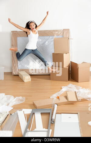 Young Asian Caucasian woman excited and happy jumping of joy with moving boxes - Stock Photo