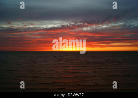 Feather clouds in setting sun above the sea - Stock Photo