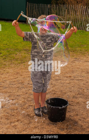 An 8 year old boy making a big bubble outdoors in the uk - Stock Photo