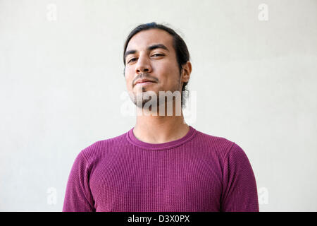 Portrait of young adult long-haired mexican-american male with expression of half-smile, doubt, and playfulness - Stock Photo