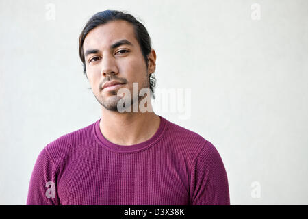 Smug and confident portrait of young long-haired adult Mexican-American male - Stock Photo