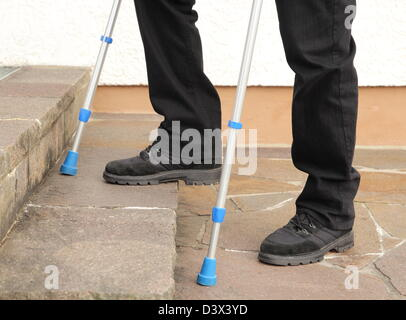 Person on crutches climbing stairs - Stock Photo