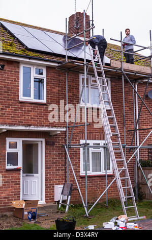 Two men fitting solar panels on the roof of a house in the Uk - Stock Photo