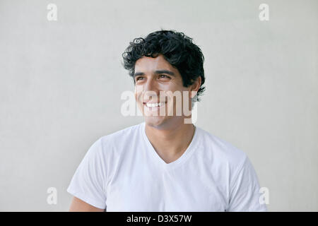 Smiling portrait of young adult mexican-american male wearing plain white t-shirt and khakis - Stock Photo