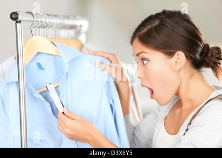 Young  mixed race Caucasian / Asian Chinese woman shopping and shocked over price tag in clothing shop - Stock Photo