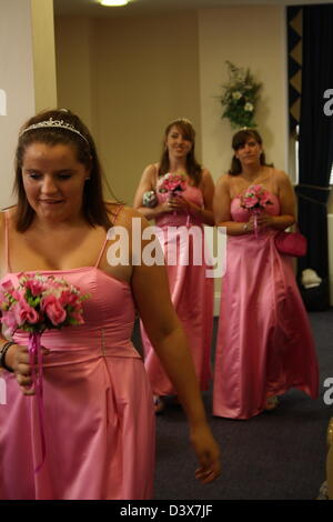Three bridesmaids walking down the isle in a registry office. - Stock Photo