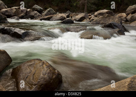 Silky slow motion river water flowing over and around large boulders in Merced River rapids of Yosemite National - Stock Photo