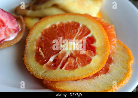 Orange Slices of blood lying on a plate brings pleasure to our taste of the fruit. - Stock Photo
