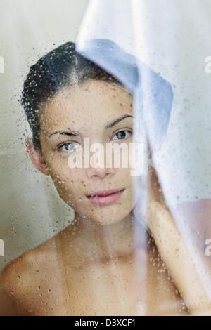 Portrait of beautiful mixed race Caucasian / Asian young shower woman bathing in bathroom