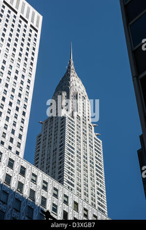 Looking up from street level at New York's Chrysler Building between nearby skyscrapers.