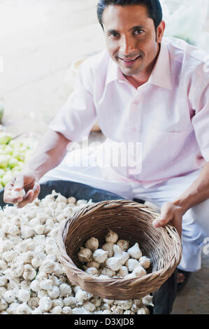indian man selling garlic from a barrow on market day. Black Bedroom Furniture Sets. Home Design Ideas