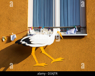 Stork and clothes hanging on a house. Customs will, from neighbors, friends hanging at the family house, when a - Stock Photo