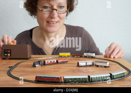 Woman playing with a Marklin model train set - Stock Photo