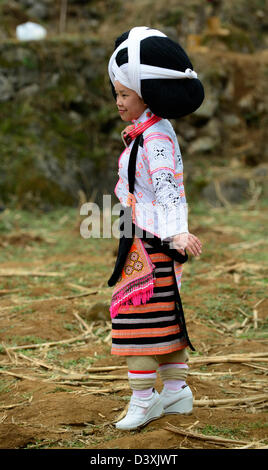 A Long Horn Miao little girl in traditional costumes dancing to celebrate the Tiao Hua festival / spring in Guizhou. - Stock Photo
