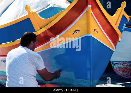 Man painting luzzu fishing boat,Marsaxlokk,Malta. - Stock Photo