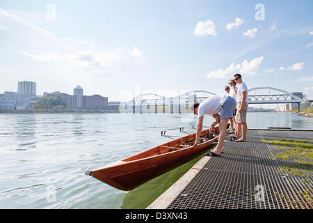 Teamwork Concept of Men Rowing Team Carrying Boat to Water