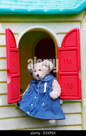Teddy bear sitting on childs playhouse windowsill - Stock Photo