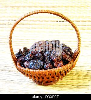 Black raisin in wicker basket on matting sunlight background - Stock Photo