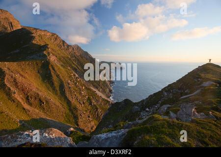 Walker dwarfed by the western cliffs of Croaghaun, Achill Island, County Mayo, Ireland - Stock Photo