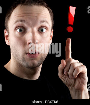 Surprised man shows red exclamation mark isolated on black background - Stock Photo