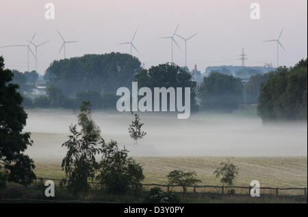 Görlsdorf, Germany, wind wheels behind a misty pasture - Stock Photo