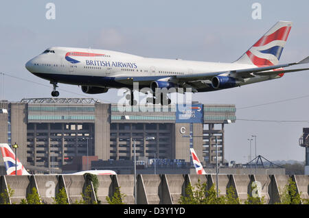 British Airways 747 coming in to land at Heathrow passing the British Airways maintenance hangar with other BA aircraft - Stock Photo