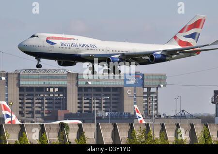 British Airways 747 plane coming in to land at Heathrow passing the British Airways maintenance hangar with other - Stock Photo