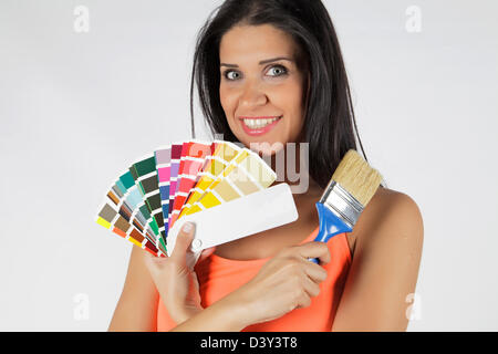 Young and attractive woman choosing colors from the palette holding a paintbrush - Stock Photo