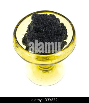 A small hand made glass goblet filled with black caviar on a white background. - Stock Photo