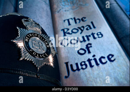 Close low view on reflective Metropolitan Police helmet badge with entrance sign to Royal Courts of Justice London - Stock Photo